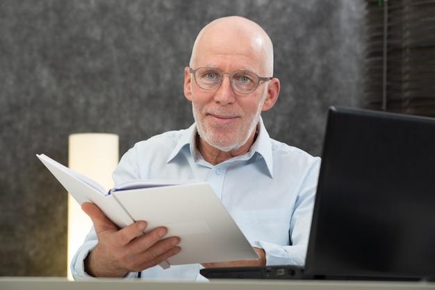 白い毛と本を読んでメガネと年配の男性人 Premium写真