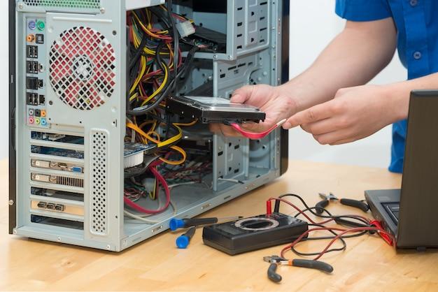 彼のオフィスで壊れたコンピューターに取り組んでいる若い技術者 Premium写真