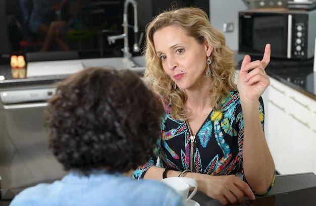 Женщина на кухне разговаривает с другом Premium Фотографии