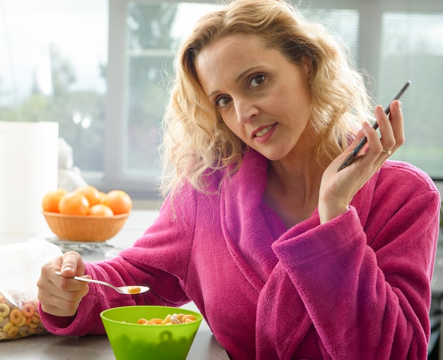 朝は穀物を食べる若いブロンドの女性 Premium写真