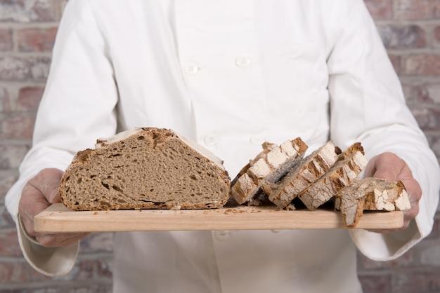 木製のテーブルに焼きたてのパンとパン屋の手 Premium写真
