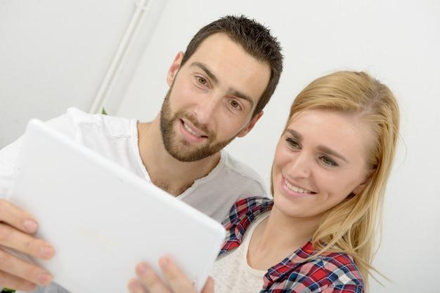 デジタルタブレットを使用して幸せな若いカップル Premium写真