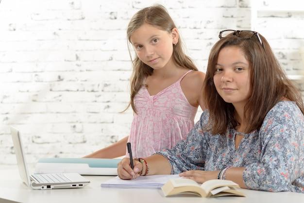 Девочка-подросток делает свою домашнюю работу со своей маленькой сестрой Premium Фотографии