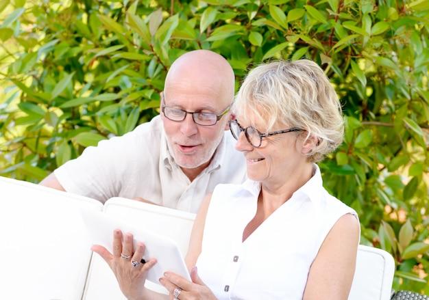 中年夫婦、笑顔、庭でタブレットを使用して Premium写真