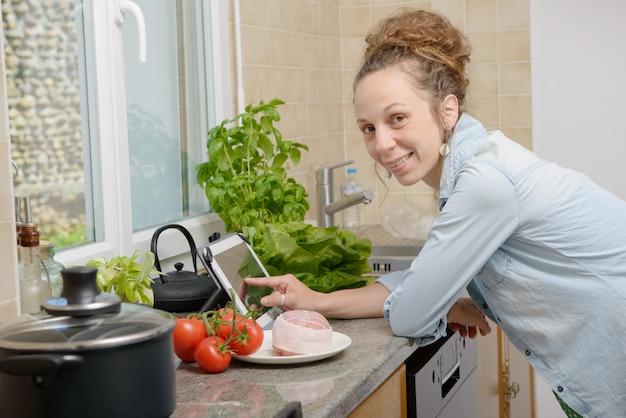 タブレットを使用して料理をする若い女性の笑みを浮かべてください。 Premium写真