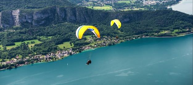 Парапланы с парапланом, прыжки вблизи озера анси во французских альпах, во франции. Premium Фотографии