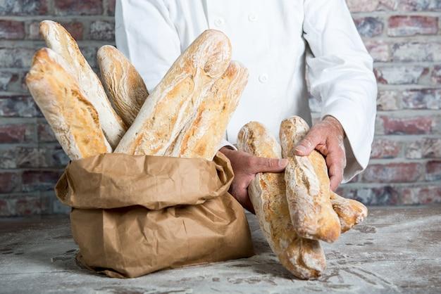 伝統的なパンフランスのバゲットを保持しているパン屋 Premium写真