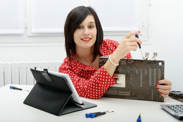 ブルネットの女性技術者はコンピューターを修理します Premium写真