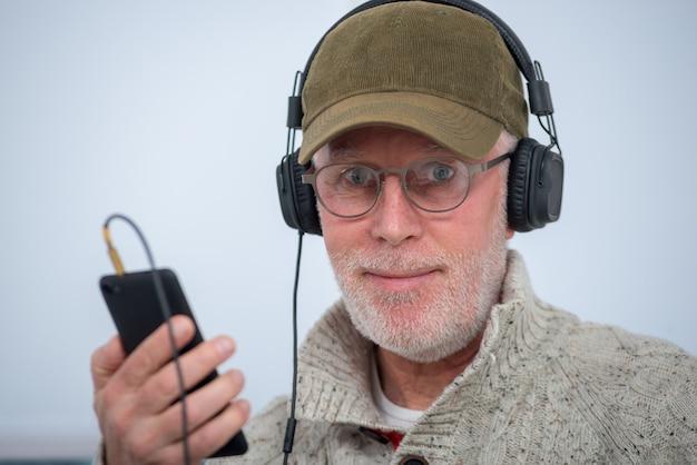 自宅で音楽を聴くヘッドフォンでキャップを持つ成熟した男 Premium写真