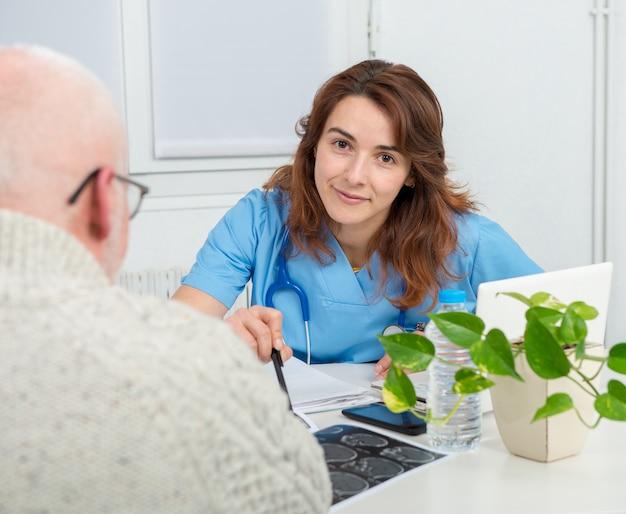 Молодая женщина-врач в офисе со своим пациентом Premium Фотографии