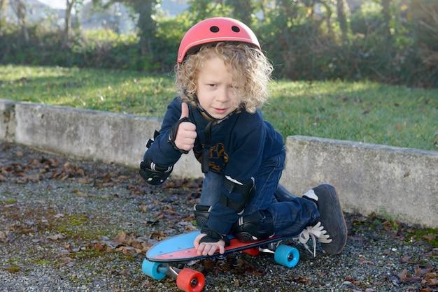 スケートボードと小さな金髪の少年 Premium写真