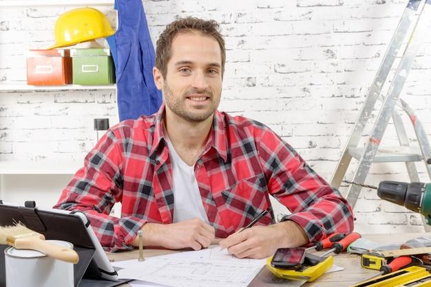 Улыбающийся плотник сидит за столом в своей студии Premium Фотографии