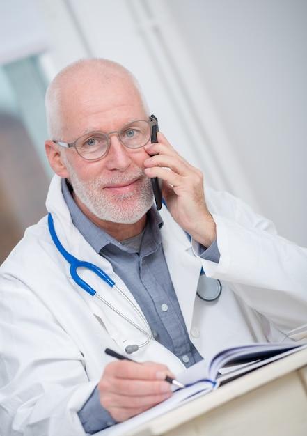 彼のオフィスで電話で成熟した医師 Premium写真