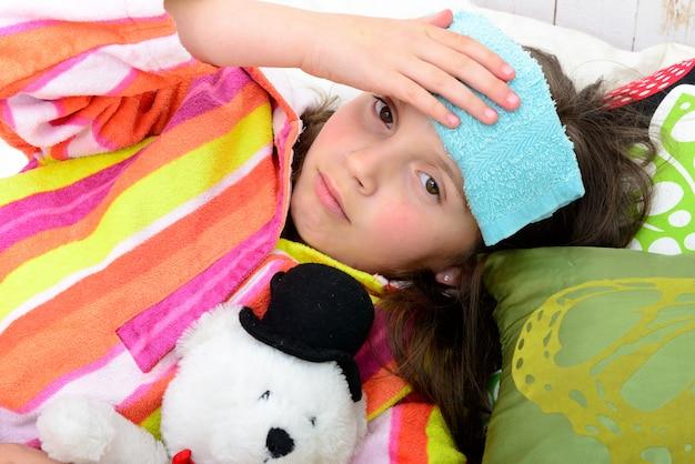 彼女のベッドの小さな女の子は頭痛がする Premium写真
