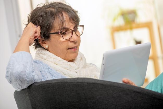 デジタルタブレットを使用して自宅でメガネを魅力的なシニアブルネットの女性 Premium写真