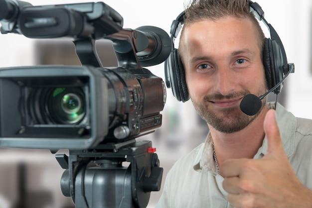 プロのビデオカメラとヘッドフォンを持つ男 Premium写真