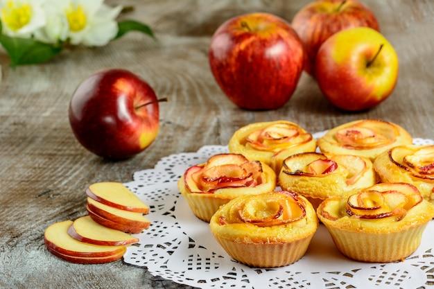 リンゴ形の木製の背景にバラのマフィン Premium写真