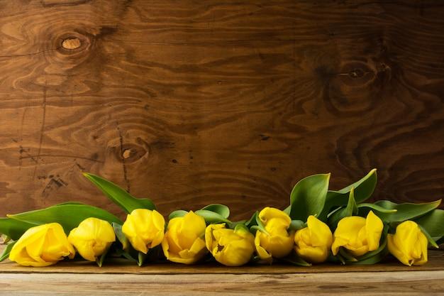 木製の表面、コピースペースに黄色のチューリップの行 Premium写真