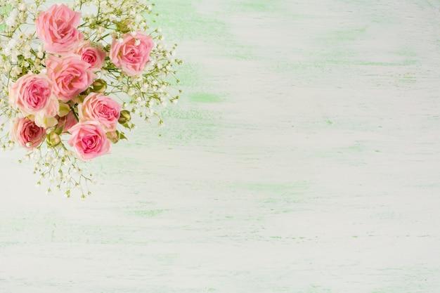 Бледно-розовые розы и белые цветы на светло-зеленом фоне Premium Фотографии