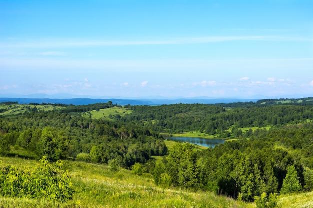 青い湖と夏の美しい丘の風景 Premium写真