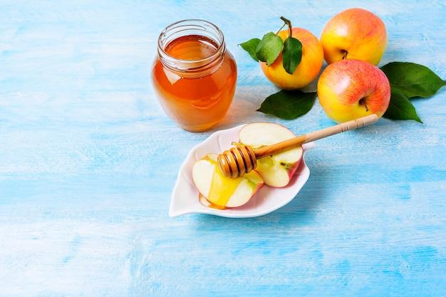 Кусочки яблока с медом на синем дереве Premium Фотографии