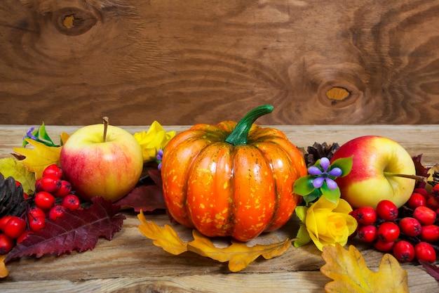 カボチャ、リンゴ、ライラックの花、ナナカマドの感謝祭の挨拶 Premium写真