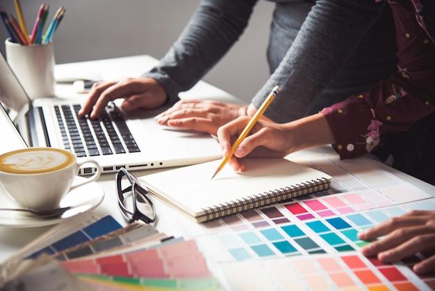Дизайнер графического креатива, креативная женщина, работающая на ноутбуке и разрабатывающая цветовой стиль идей Premium Фотографии