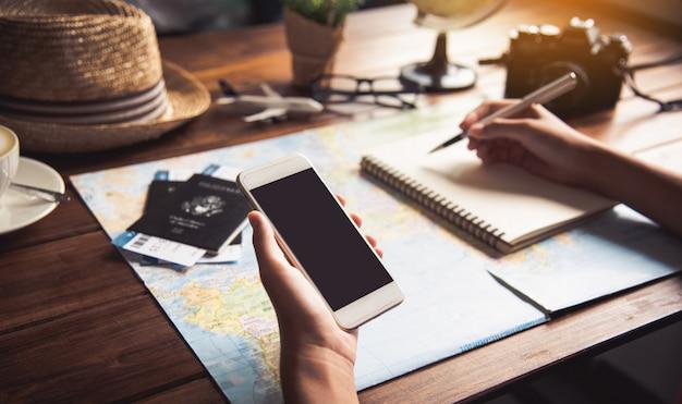 旅行者は、地図上のルートを検索し、インターネット上の情報を検索することで旅行を計画しています。 Premium写真