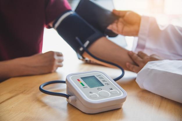 Доктор измеряет артериальное давление у своего пациента Premium Фотографии