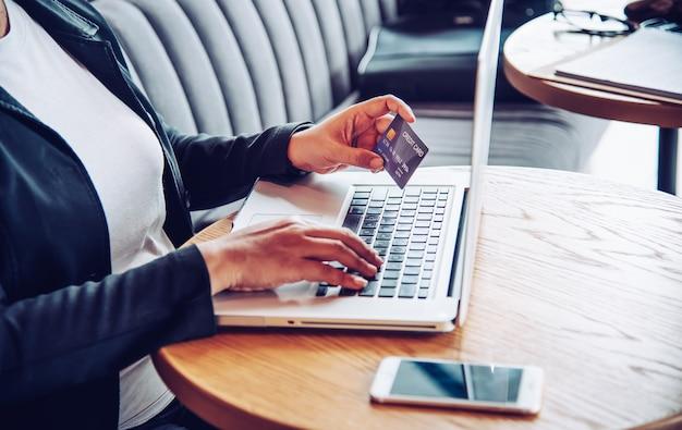 クレジットカードを手に持って、ラップトップデバイスを使用してオンラインで購入し、金融取引を行う製品に関する情報を見つける手。 Premium写真