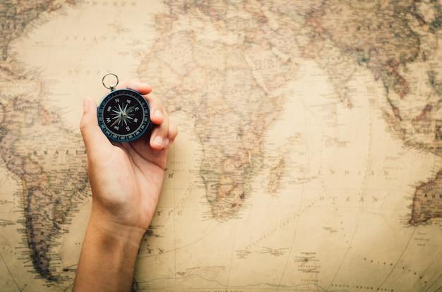 Туристы держат компас и размещают место на карте мира. Premium Фотографии