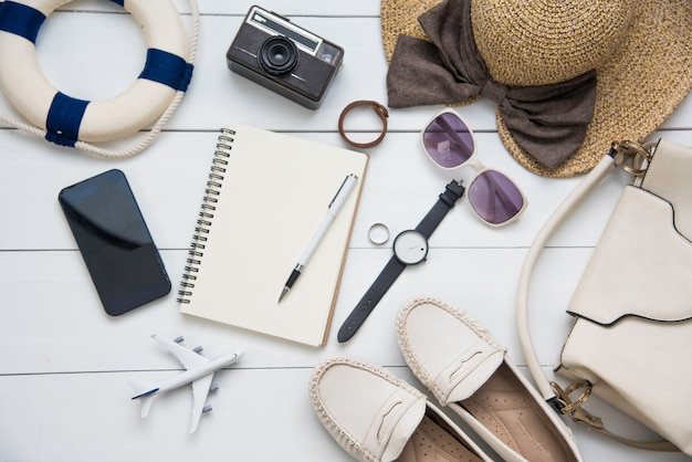 女性用トラベルアクセサリーコスチューム。パスポート、白い木の床で旅行のために準備された旅行地図の費用 Premium写真
