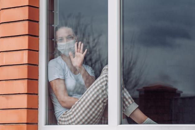 Домашний карантин. кавказская женщина, сидя у окна в медицинской маске, глядя, хочет выйти. защита от коронавирусной инфекции. Premium Фотографии