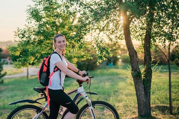 バックパックとスポーツ服でスポーティな若いブロンドの女の子は自転車に乗るし、カメラに笑顔 Premium写真