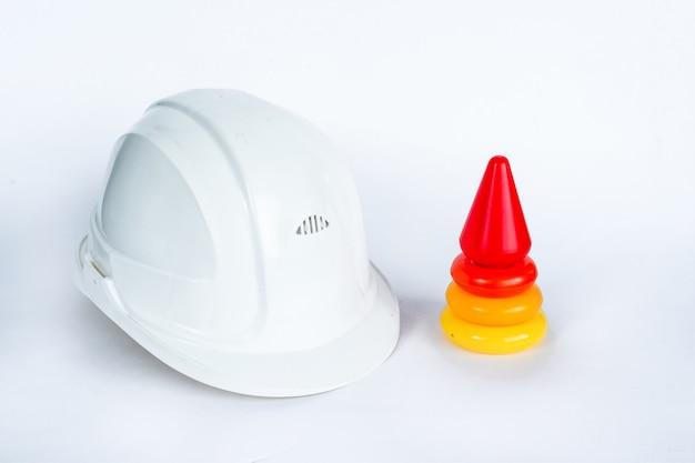 Цветная детская пирамида и белый шлем инженера-строителя на белом фоне изолированные Premium Фотографии