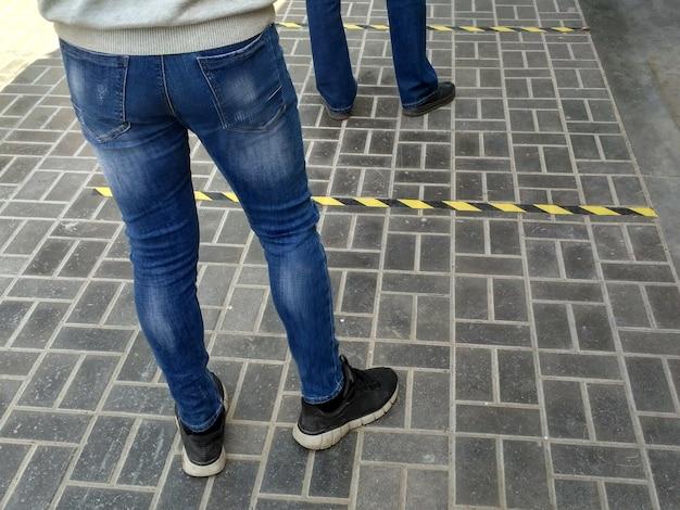 路上の店のキュー。社会的距離。安全に食料品店に入るのを待っている人々の足。コロナウイルスのパンデミックの際の、床からの距離を確保するための安全なマーキング。 Premium写真