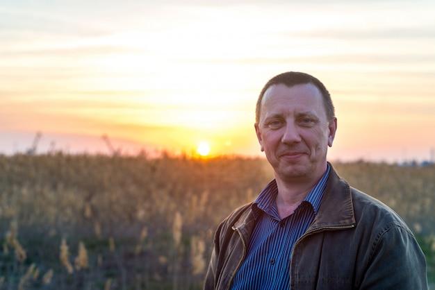 Счастливый кавказский фермер-самец гордо стоит перед своими пшеничными полями после рабочего дня. человек улыбается хороший урожай на закате. концепция выращивания хлеба, земледелия. копировать пространство Premium Фотографии