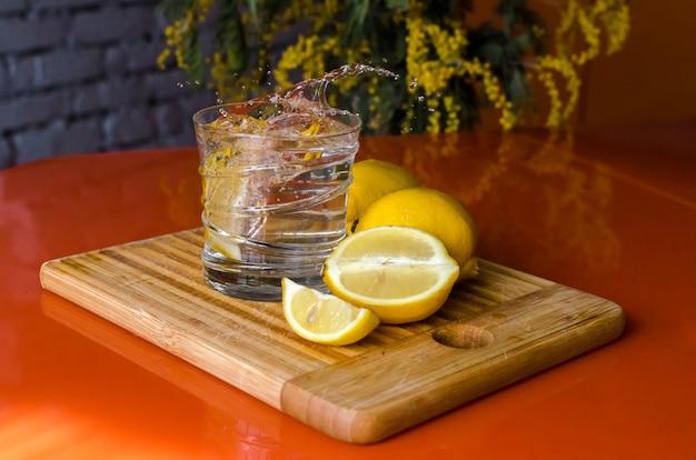 Цитрусовый лимонад. стакан освежающей воды с кусочками лимона, чтобы утолить жажду Premium Фотографии