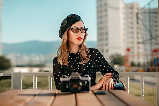 路上でポーズをとって彼女の手で古いカメラを持つヴィンテージ黒水玉ドレスの若い女性 Premium写真