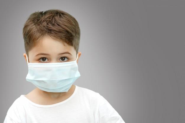 Маленький кавказский мальчик в медицинской маске на изолированных фоне Premium Фотографии