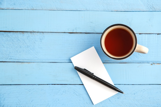 Чашка напитка и бумажный блокнот с черной ручкой на синем дереве Premium Фотографии