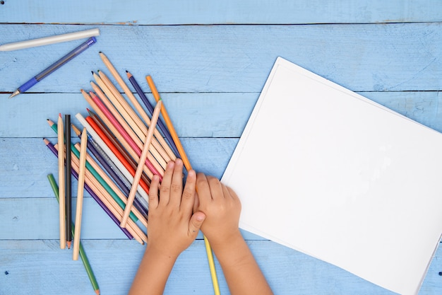 青いテーブルのアルバムで子供たちの手が鉛筆で描く Premium写真