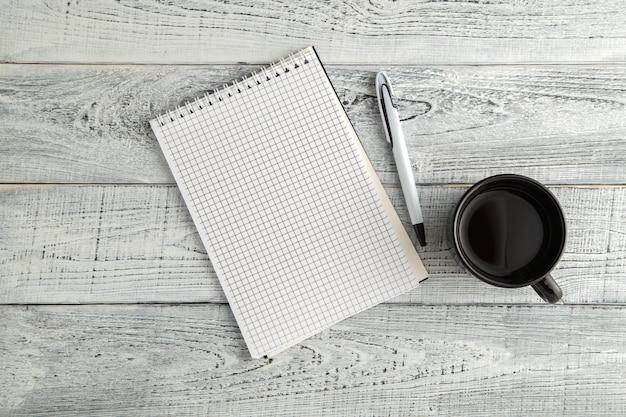 紙のノート、ペン、ヴィンテージのぼろぼろの白い木の上面にお茶やコーヒーのカップ Premium写真