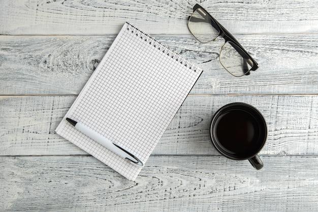 紙のノート、ペン、お茶やコーヒー、ビンテージのぼろぼろの白い木、上面に光学ガラスのカップ Premium写真