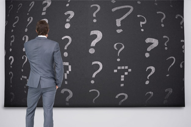 疑問符を見ているビジネスマンの背面図 無料写真