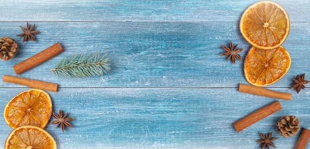 Новогодний фон: сушеные апельсины, анисовые звезды, палочки корицы, веточка ели, на синем деревянном фоне Premium Фотографии
