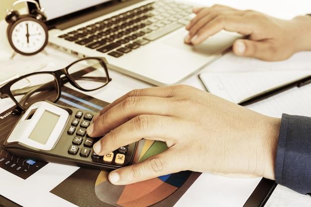 ビジネス会計計画コンセプト、ビジネスを行うための電卓を持つデスクトップのラップトップコンピューターに取り組んで、 Premium写真