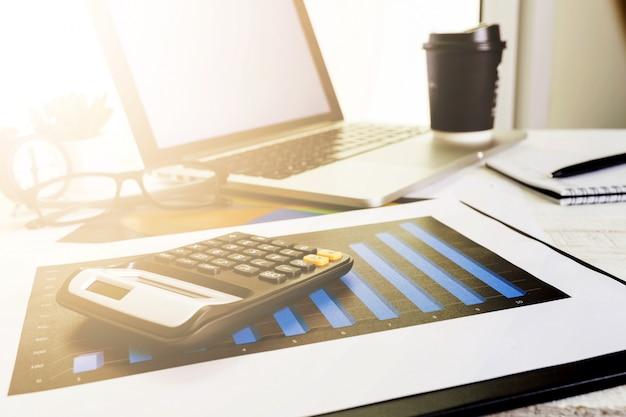 ビジネスを行うための電卓とデスクトップのラップトップコンピューターに取り組んで、 Premium写真