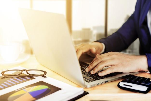 ビジネス会計計画コンセプト、ビジネスを作るための電卓とデスクトップラップトップコンピューターで作業、木製デスクビジネス投資顧問のラップトップコンピューターで作業するビジネスの男の手。 Premium写真