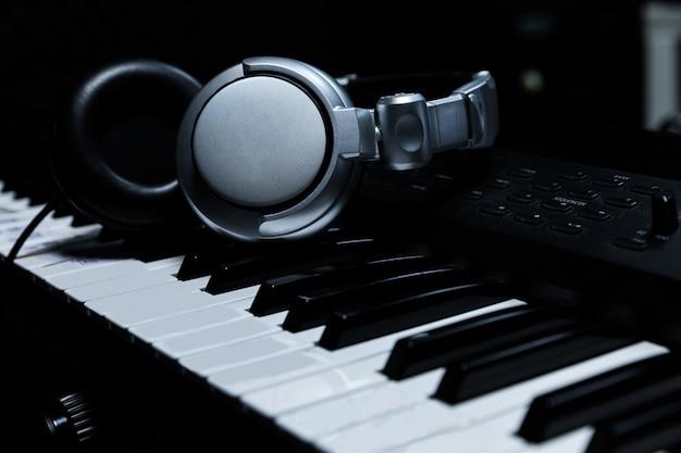 Клавиатура рояля с наушниками для музыки, наушники на клавиатуре рояля, конец вверх, наушники на предпосылке электрического рояля предпосылкой музыкальных инструментов. Premium Фотографии
